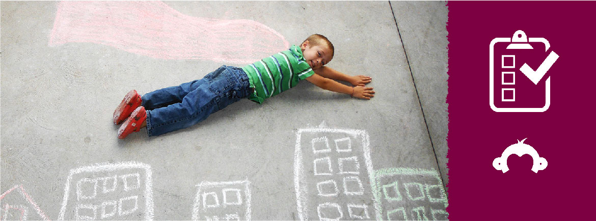boy laying on ground flying over chalk drawn buildings