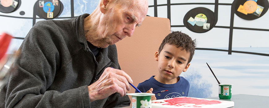 elder man with boy painting