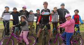 Kids on bikes pose with Don Patterson at the new bike park.