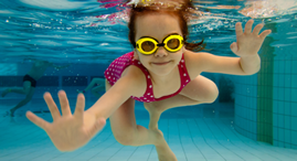 Girl under water with yellow goggles.