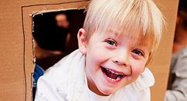 A blonde boy plays in a box-fort at YMCA Child Care.