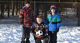 Boys playing soccer in snow.