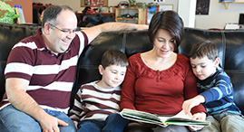 A YMCA family reading a book together.