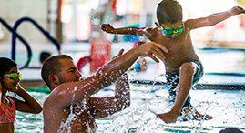 A father catches his son as he jumps into the YMCA pool.