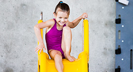 A girl in a purple swimsuit goes down a slide at a YMCA pool.
