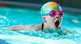 A girl wearing a swim cap and goggles swims laps in a YMCA pool.