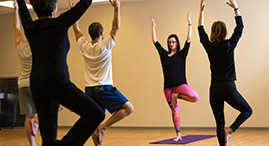 A YMCA group fitness yoga class doing tree pose.