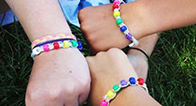 Kids showing off their YMCA Camp Value Beads on their wrists.