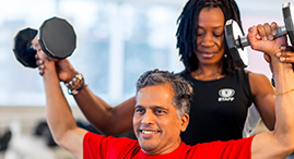 A YMCA personal trainer works with a member on weight lifting exercises.