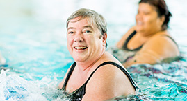 Two older ladies doing aquafit in a YMCA pool.