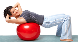 A young woman does crunches on a YMCA exercise ball.