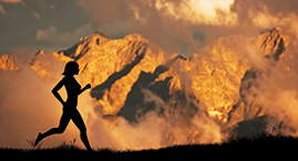 Silhouette of a woman running in front of mountains.