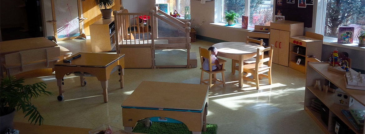 Child Care Centre sectioned off with different areas of activities.  There are three large window with an outside view.