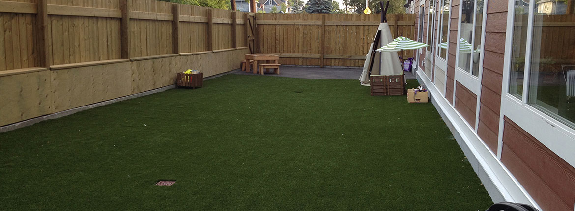 Child Care Centre, wooden fenced outdoor with artificial turf, sectioned off with a seating and tipi play area