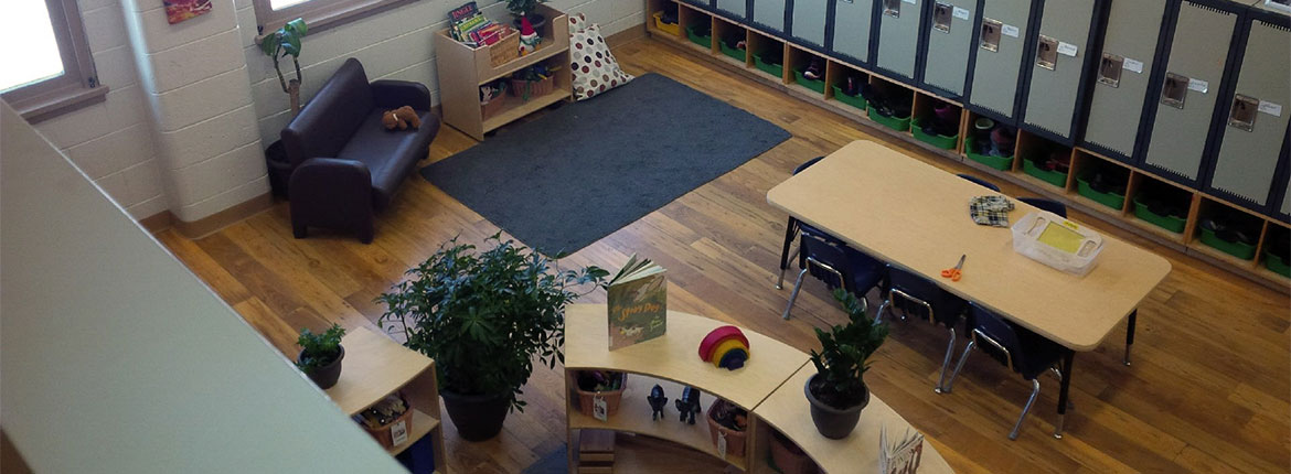 Second floor view overlook the Child Care Centre sectioned off with seating, playing and storage area.
