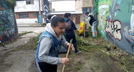 Valentina in an alley, cleaning up debris with other YMCA participants.