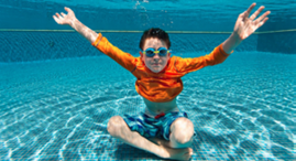 Boy wearing an orange shirt and goggles, floating inside a pool.