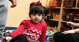 Young child with a red sweater sitting on a carpet in a YMCA Child Care centre.