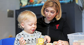 Young child and YMCA staff member playing with blocks in a YMCA Child Care centre.