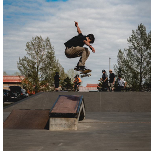 Photo of Aaron on a jump at a skatepark