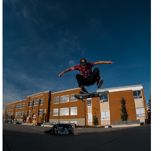 Photo of Mitchell C on a jump, with a school in the background