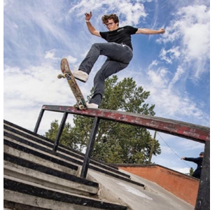 Photo of Mitchell G on a skateboard, sliding down a staircase at a skatepark