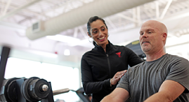 YMCA personal trainer helping YMCA member during a workout.