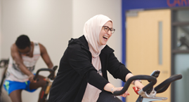 Woman sitting on a stationary bike in a cycle class, laughing.