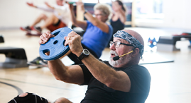 YMCA fitness instructor wearing a mic, leading a group fitness class.