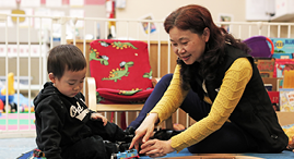 A child sitting on the floor, playing with a toy along side a YMCA Child Care staff member.