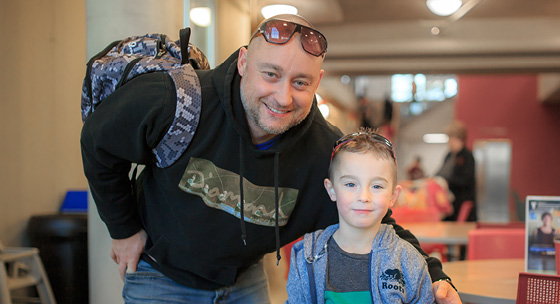 Father and son standing together in a YMCA Child Care centre.